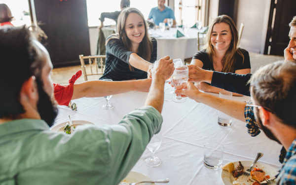 people cheersing around a table