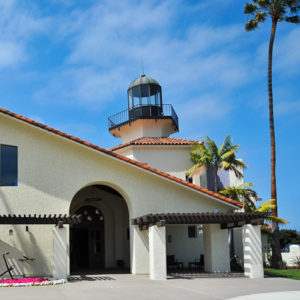 a building with a lighthouse attached and palm trees around it